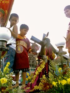Children waiting for the image of the Black Nazarene to pass by P. Burgos Avenue in Manila