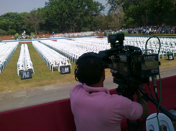 ABS-CBN cameraman looking over the seating for UP graduates (Shot by Anjo Bagaoisan)