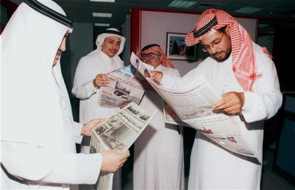 Saudi nationals in Riyadh read the papers 2 days after 9/11. (AFP/Getty via Canada.com)