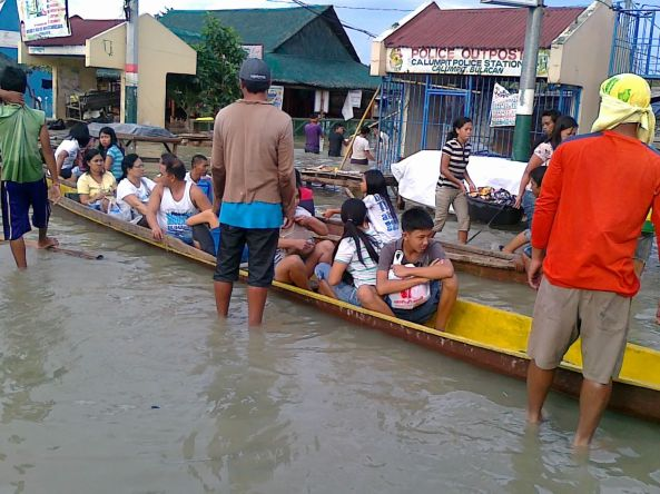 People riding boats over Calumpit, Bulacan floods October 2011. Shot by Anjo Bagaoisan