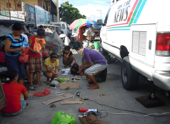 Residents charging phones with ABS-CBN's ENG van in flooded Calumpit Bulacan October 2011 (Shot by Chito Concepcion)