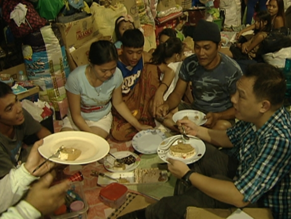Alvin Elchico with evacuees eating Noche Buena (Shot by Jonathan Asedillo, ABS-CBN News)