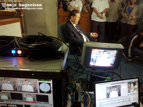 Senate President Juan Ponce Enrile being interviewed from the Senate on GMA 7 24 Oras, as a monitor shows Sen. Antonio Trillanes being interviewed on ABS-CBN TV Patrol (Shot Sept 19, 2012 by Anjo Bagaoisan)