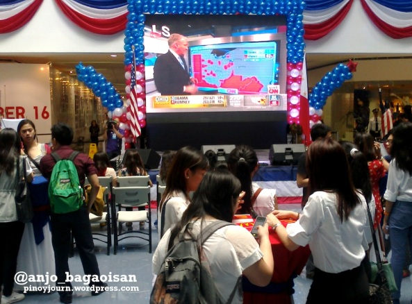 Filipinos at a Quezon City mall watch John King work the touchscreen on CNN during election night (Shot by Anjo Bagaoisan)