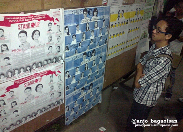 A student looks at the slate posters of UP Diliman's STAND-UP, ALYANSA, and KAISA 2013 USC bets (Shot by Anjo Bagaoisan)