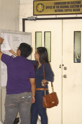 Anjo Bagaoisan and Jenny Reyes browsing the media absentee voters' lists at the Comelec NCR office (Shot by Chito Concepcion)