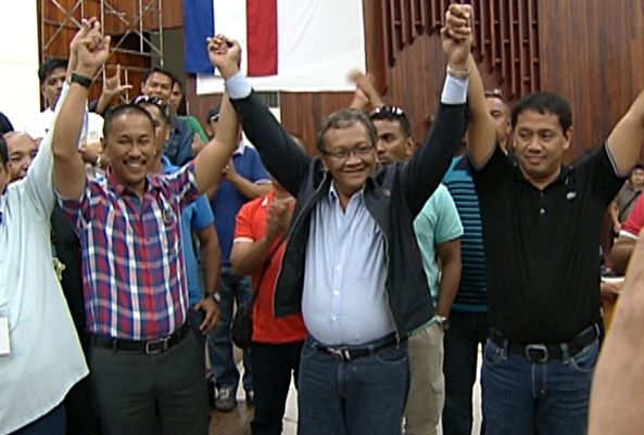 Comelec Maguindanao supervisor Atty. Nasib Yasin raises the hands of Toto Mangudadatu and Lester Sinsuat, winners of the 2013 gubernatorial race, 15 May 2013. (Shot by Gani Taoatao, ABS-CBN News)