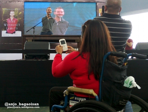A woman in a wheelchair takes a picture of motivational speaker Nick Vujicic at his speaking engagement at the SM Mall of Asia (Shot by Anjo Bagaoisan, May 20, 2013)