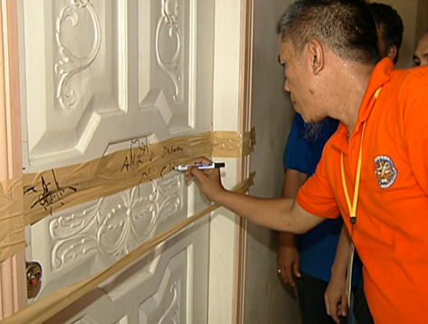 Comelec election officer of Datu Saudi, Maguindanao signs sealed door of room where PCOS machines and election paraphernalia are stored, May 2013.(Shot by Gani Taoatao, ABS-CBN News)