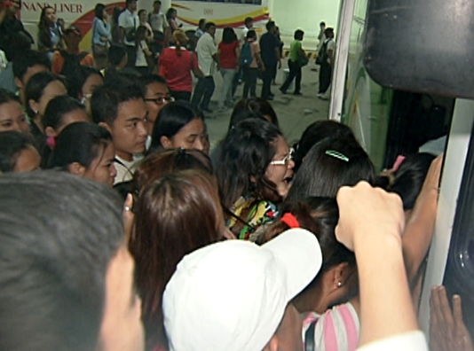 Commuters going home jostle in an attempt to board a bus at the Southwest Integrated Bus Terminal on its first night of operation. (Shot by Evart Villar, ABS-CBN News)