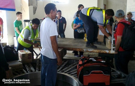 Airport staff drop baggage directly at non-working conveyor belt at Tacloban City Airport arrival area (Shot Nov. 26, 2013 by Anjo Bagaoisan)
