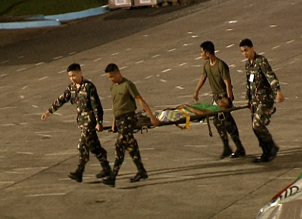 Soldiers carry an injured survivor of Typhoon Yolanda in a stretcher at Villamor Airbase (Shot by Nestor Conato, ABS-CBN News)