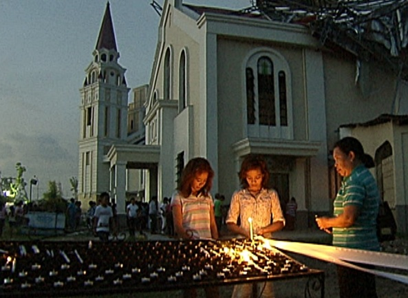Mourners light candles at the mass grave beside Palo Cathedral in Leyte. (Shot by Brian Pimentel, ABS-CBN News)