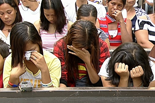 Mass attendees cry during a memorial service in Palo, Leyte at the first-month mark since Typhoon Yolanda. (Shot by Brian Pimentel, ABS-CBN News)