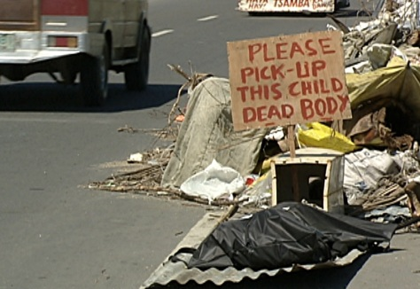 A sign is placed over a corpse in a Tacloban street asking for it to be picked up. (Shot by Evart Villar, ABS-CBN News)