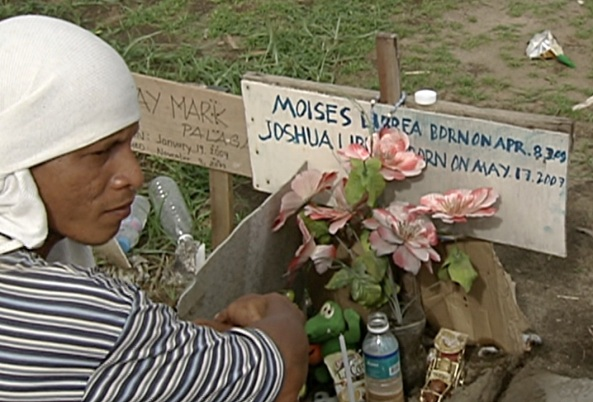 Armand Librea of Palo, Leyte at the grave of his wife and sons, who died during Yolanda. (Shot  by Evart Villar, ABS-CBN News)