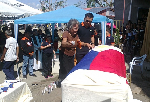 Florentina Sison breaks down as she blesses a casket memorializing her son and four other fire men killed during Typhoon Yolanda. (Shot by Anjo Bagaoisan)