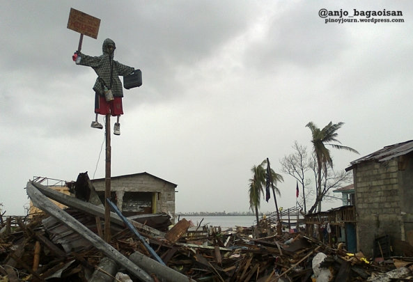 "A dummy waves a placard written with ""Please help. We need new house"" above the debris of Magallanes district in Tacloban City. (Shot by Anjo Bagaoisan)"