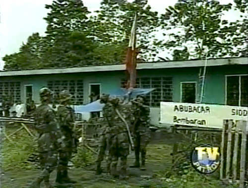Soldiers raise the Philippine flag over a school in Camp Abubakar after its capture by the military in July 2000 (Grab from ABS-CBN's TV Patrol)