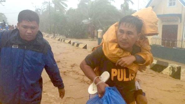 ABS-CBN DZMM reporter Dennis Datu follows a police man rescuing a child stranded during floods brought by Typhoon Lando in San Luis, Aurora (Shot from Dennis Datu)