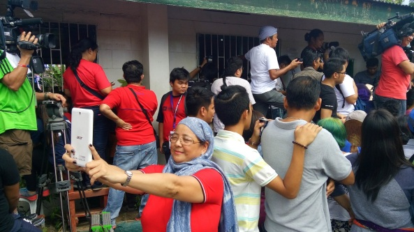 A Davao City resident takes a selfie with the crowd outside the precinct Duterte votes in (Shot by Anjo Bagaoisan)