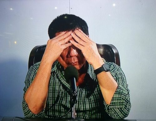 Duterte covers his face at a press conference in Davao City. Shot by ABS-CBN News