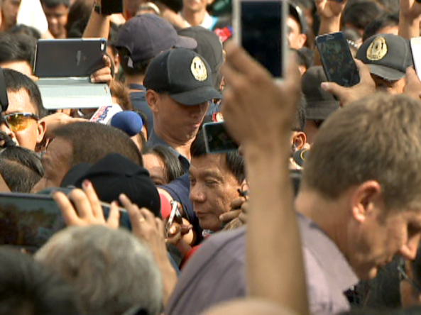 Duterte surrounded by crowd and cellphone cams as he arrives to vote at Daniel Aguinaldo High School in Davao (Shot by Dong Plaza, ABS-CBN News)