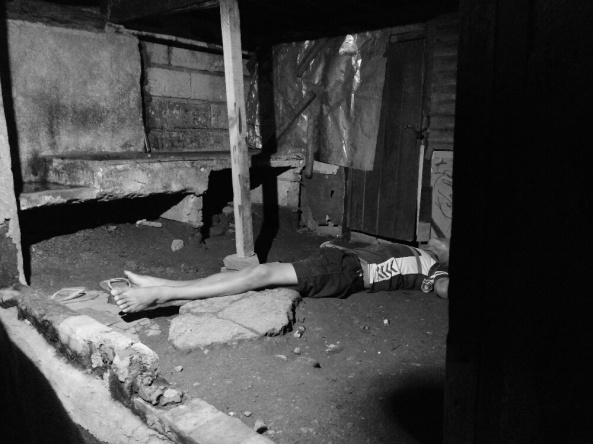 Body of AWOL policeman suspected of dealing drugs and killed in a buy-bust lies below a house in Bulacan. August 2, 2016. (Shot by Anjo Bagaoisan)