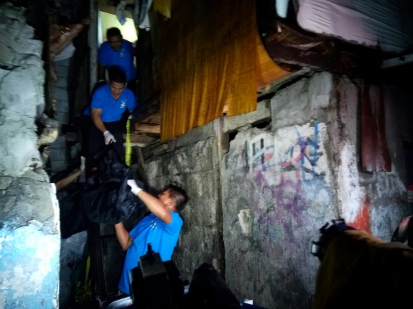 Funeral parlor workers carry out bodies of suspected drug users killed in police op from a house in Pasay City. August 9, 2016. (Shot by Anjo Bagaoisan)