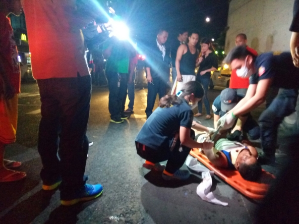 Emergency rescuers lift man injured in motorcycle crash, Philcoa, Commonwealth, Quezon City, August 1, 2016 (Shot by Anjo Bagaoisan)