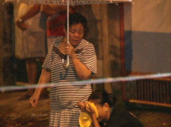 Gloria Dela Cruz talks to her crying daughter outside police line where Gloria's husband lay shot by unidentified gunmen in Batasan Hills, Quezon City, August 24 (Shot by Melchor Platero, ABS-CBN News)