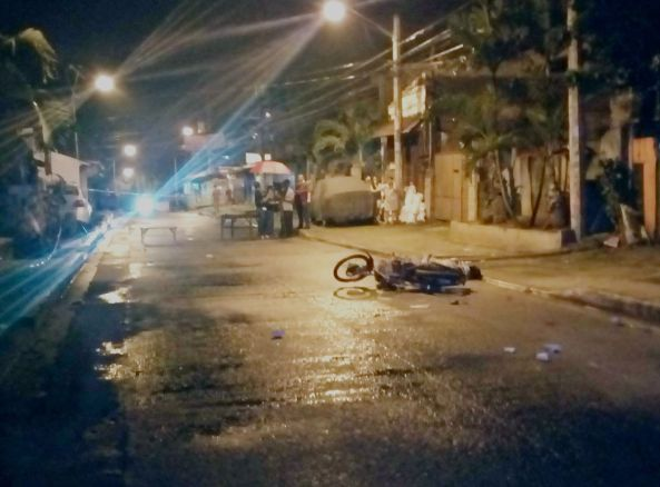 Motorcycle driven by Arnaldo Dela Cruz lies down at Executive Road after Dela Cruz was shot by unidentified gunmen in Batasan Hills, Quezon City, August 24 (Shot by Anjo Bagaoisan)