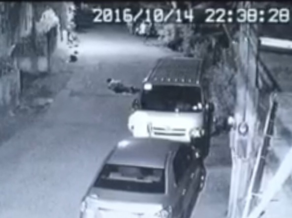 A bystander looks on at Nick Russell Oniot's body after he collapsed on the street after being stabbed. Grab from CCTV of Brgy Central Signal Village, Taguig