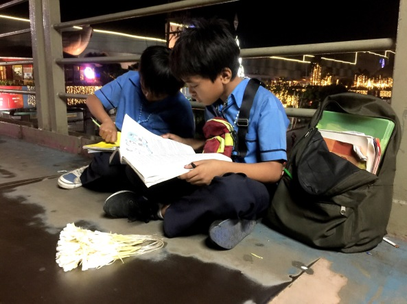 Sampaguita vendor brothers Melvin and Marlon Mendoza studying at an overpass in EDSA (Shot by Anjo Bagaoisan)