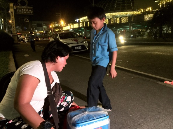 Sampaguita vendor Rochelle Asadon fixes the shoes of her son Melvin. (Shot by Anjo Bagaoisan)