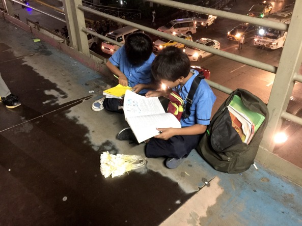 Melvin and Marlon Mendoza studying while selling sampaguitas at an overpass (Shot by Anjo Bagaoisan)